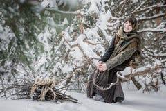 坐与在冬天森林字符的草丛的老衣裳的少妇从童话 免版税库存照片