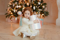 坐与在圣诞节的一件礼物的卷曲小女孩 免版税库存图片