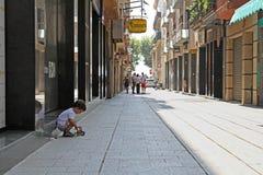 坐与在城市胡同的一个玩具的一个小男孩在卡莱利亚 免版税库存照片