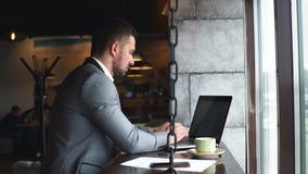 坐与在完成遥远的工作的咖啡馆的膝上型计算机的一位严肃的有胡子的人企业家的侧视图 股票视频