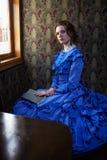 坐与在小轿车的书的蓝色葡萄酒礼服的少妇  免版税图库摄影