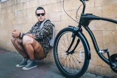 坐与在街道每日定期生活方式的固定的齿轮自行车的英俊的年轻旅游人 免版税库存照片