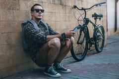坐与在街道每日定期生活方式的固定的齿轮自行车的年轻旅客人 免版税库存照片