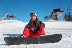 坐与在雪的雪板的卷曲女孩在滑雪电缆车附近 免版税图库摄影