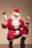 坐与在他的左手的响铃的圣诞老人 库存照片