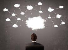 坐与在他的头上的云彩技术的商人 免版税库存照片