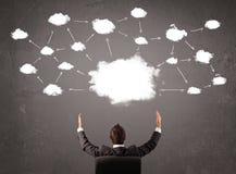 坐与在他的头上的云彩技术的商人 免版税库存图片