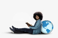坐与地球和书的蓬松卷发学生 库存照片