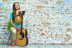 坐与声学吉他的秀丽妇女 图库摄影