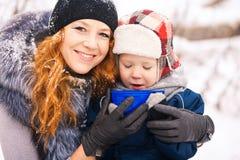 坐与外面年轻美丽的母亲的婴孩 免版税库存照片