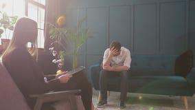 坐与女性心理学家的人客户在舒适的长沙发在心理会议期间在蓝色办公室 股票视频