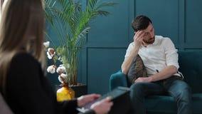 坐与女性心理学家的人客户在舒适的长沙发在心理会议期间在蓝色办公室 影视素材