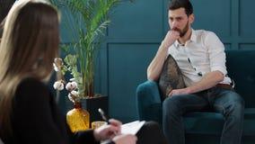 坐与女性心理学家的人客户在舒适的长沙发在心理会议期间在蓝色办公室 股票录像