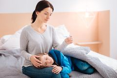坐与她不适的孩子的被集中的母亲 免版税图库摄影
