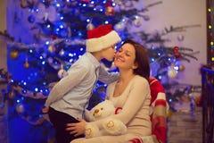 坐与她愉快的儿子的相当年轻母亲画象在sa中 免版税库存图片