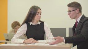 坐与她的上司的画象年轻女性秘书在办公室 改正女孩的报告的人 E 股票录像