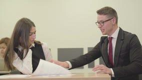 坐与她的上司的画象年轻秘书在办公室 改正女孩的报告的人 E 股票视频