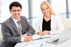 坐与她的同事的成功的女商人在办公室 免版税库存图片