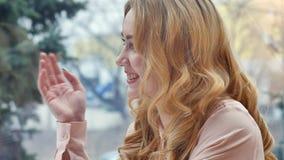 坐与她的咖啡馆的朋友的年轻白肤金发的女孩 库存图片