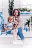 坐与她的姐妹的女孩在圣诞树和微笑附近 库存图片