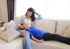 坐与她的孩子的母亲在她的在沙发的膝部放置在客厅 库存图片