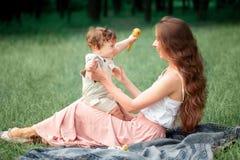 坐与她的小儿子的年轻美丽的母亲反对绿草 有她的男婴的愉快的妇女在晴朗一个的夏天 图库摄影