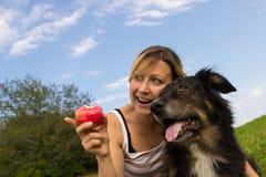 坐与她的狗的妇女 免版税库存图片