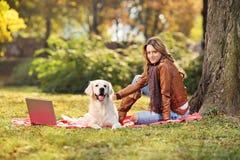 坐与她的狗的美丽的女孩在公园 免版税库存照片