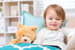 坐与她的玩具熊的愉快的小孩女孩 库存照片