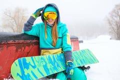 坐与她的雪板的美丽的愉快的年轻挡雪板 库存图片