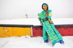 坐与她的雪板的美丽的愉快的年轻挡雪板 免版税图库摄影