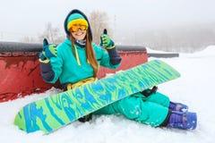 坐与她的雪板的美丽的愉快的年轻挡雪板 免版税库存照片