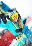 坐与她的雪板的美丽的愉快的年轻挡雪板 图库摄影