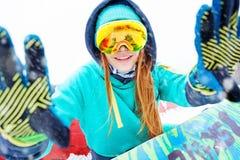 坐与她的雪板的美丽的愉快的年轻挡雪板 免版税库存图片
