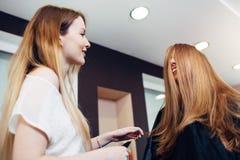 坐与她的面孔的发式专家和女性顾客盖由谈话和笑在美容院的头发 库存照片
