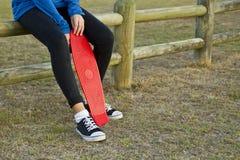坐与她的滑板的少妇 库存图片