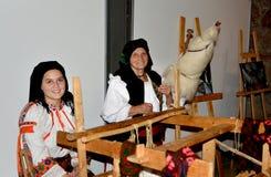 坐与妇女的传统晚上转动的羊毛 免版税库存照片