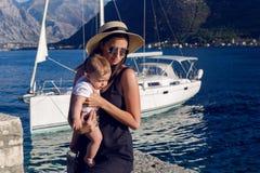 坐与婴孩的帽子的女孩在一条大小船旁边 免版税库存图片