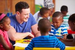 坐与学龄前孩子的志愿老师在教室 免版税库存照片