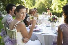 坐与客人的美丽的新娘在婚礼表上 免版税库存图片