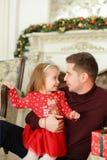 坐与小女儿近的装饰的壁炉和保留礼物的欧洲父亲 免版税库存照片