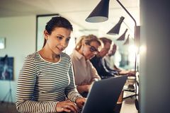 坐与工作同事的微笑的年轻设计师使用lapt 免版税库存照片