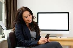 坐与巧妙的电话和计算机的女商人 库存图片