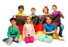 坐与德国旗子的小组七个孩子 库存照片