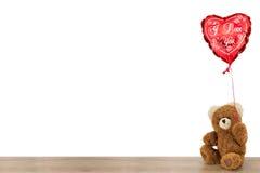 坐与心脏气球的玩具熊 免版税图库摄影