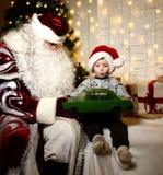 坐与愉快的矮小的逗人喜爱的男婴孩子的圣诞老人在圣诞树附近 库存图片