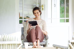 坐与数字式片剂的微笑的妇女 免版税库存图片