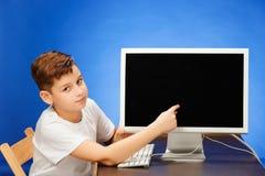 坐与显示器膝上型计算机的学龄男孩在演播室 库存照片