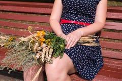坐与杂色的草花束的少妇在Macovei cel期间 免版税库存图片