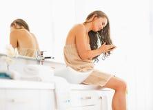 坐与湿头发的少妇在卫生间里 免版税库存照片